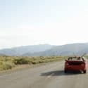 a carefree couple drives down a desert road in a red convertible