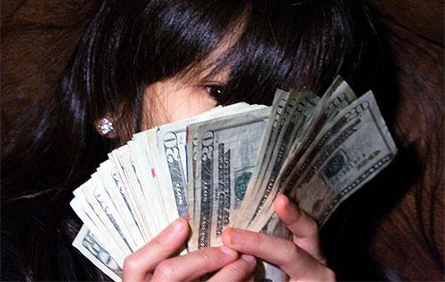 hiding face with money