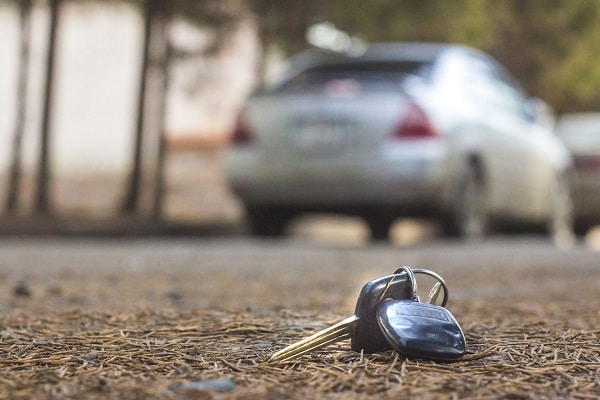 a set of car keys sits forgotten on the ground outside behind a car