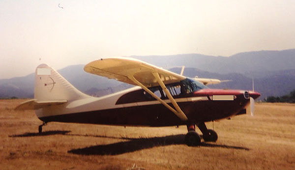plane in the field with mountains in background