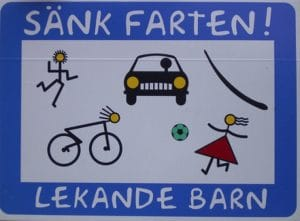 "a swedish-language road sign says ""sank farten; lekande barn"" with drawings of kids playing and cyclists in the road"